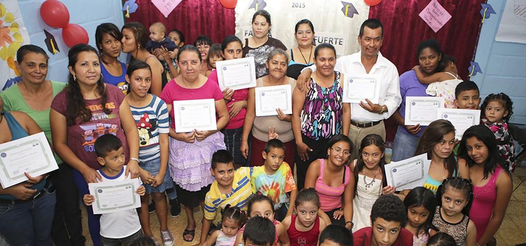 Las orgullosas familias muestran su certificado de graduación del taller.